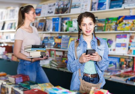 Portrait of attractive girl picking textbooks and talking on telephone in shop