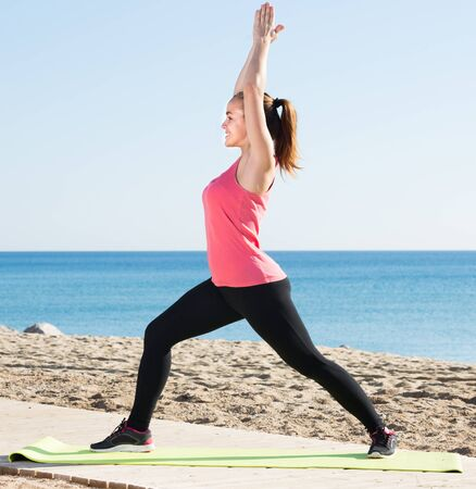 Smiling young woman doing exercises at sea beach Zdjęcie Seryjne