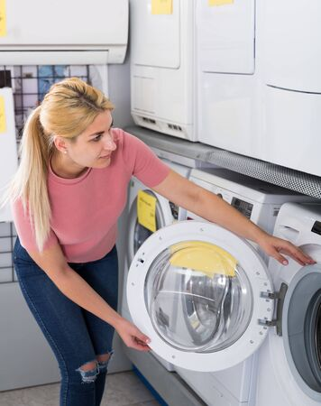 Young female customer selecting new washer in household appliances store