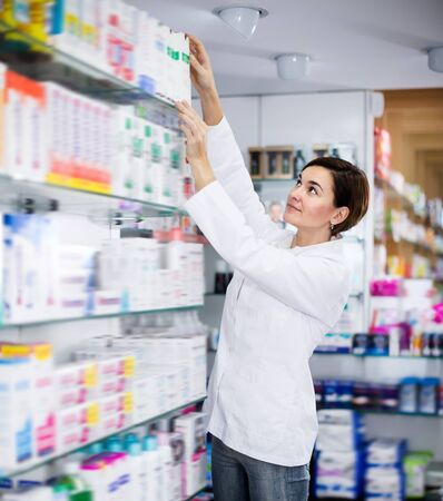 Glad female offering reliable medicine in pharmacy