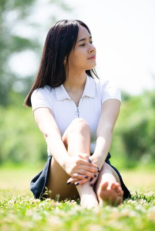 Girl sitting on the green grass in the park