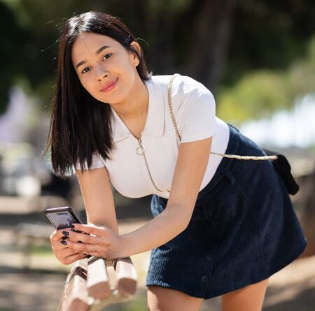 Smiling young girl sitting on a bench and chatting on smartphone in park
