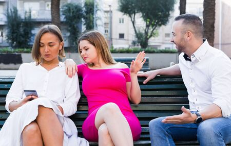Girlfriends are rejecting stranger man who wants acquintance with them in the park. Фото со стока