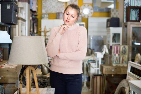 positive woman buyer standing in furniture shop choosing modern torchere indoors