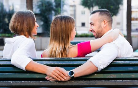 Image of the love triangle between young cheerful people outdoor