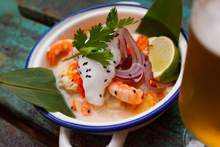 Shrimp ceviche in Vietnamese style with coconut milk, vegetables and lime in enamel bowl with handles
