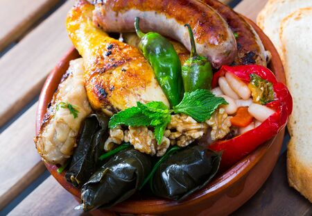 Bulgarian cuisine. Kapama - mixed stewed plate from meat, sausages, stuffed cabbage, grape leaves and bell pepper Stockfoto