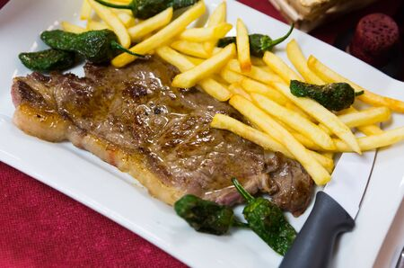 Appetizing beef steak with side dish of fried potatoes and jalapenos Stockfoto