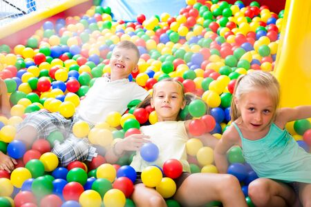 small russian children playing together in pool with plastic multicolored balls