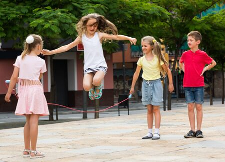 group of cheerful children skipping together with jumping rope on urban playground Zdjęcie Seryjne