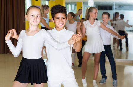 Group of positive smiling children dancing salsa in school