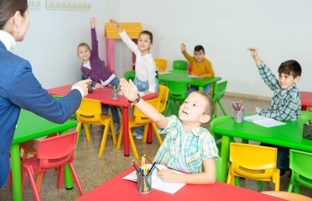 Group of cheerful studious pupils studying in elementary school, raising hands to answer female teacher