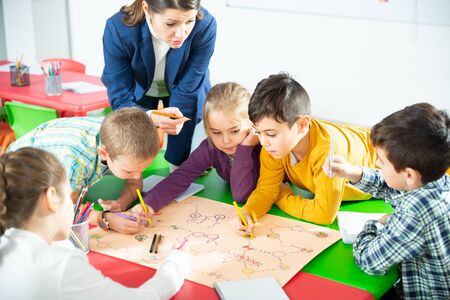 Teacher and collective of elementary age children draw together a board game Фото со стока