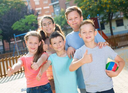 Kids posing at the playground together and thumbs up