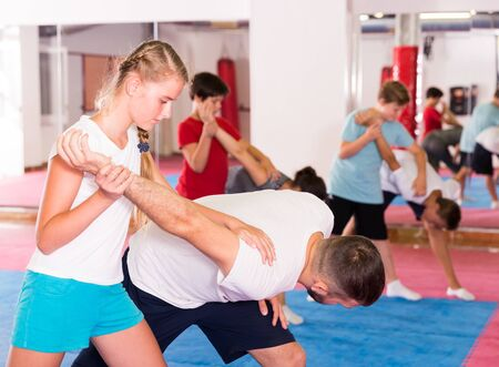 Adult and teen people practicing self defence technique in pairs at gym