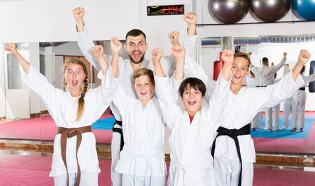 Portrait of happy children and male coach in kimonos before karate training