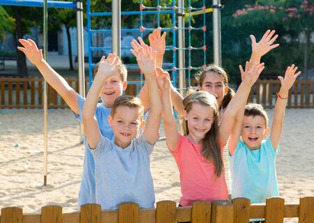 Cheerful kids posing at the playground together and hands up