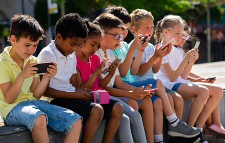 Group of smiling children sitting at urban street with mobile devices Stock Photo