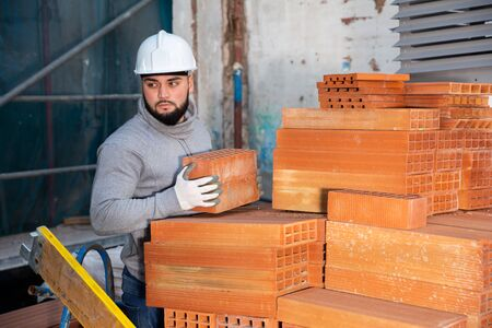 Serious young man working on his house renovations, stacking red bricks