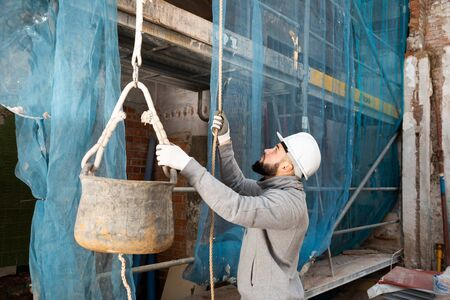 Young bearded man working at building site, raising bucket with construction mortar on rope