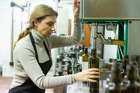 Skilled woman engaged in olive oil production, controlling process of bottling of finished product in glass bottles