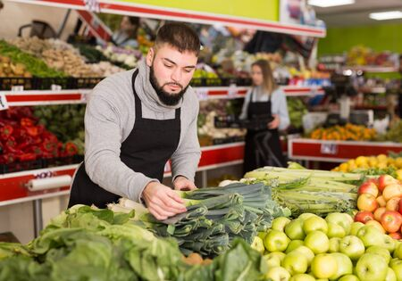 Male shop assistant in apron lays fresh leek in supermarket