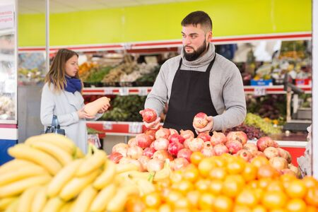 Positive man in apron selling ripe pomegranates