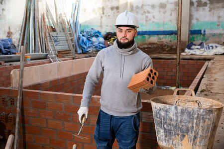 Confident young builder working with red brick on overhauls of house Foto de archivo