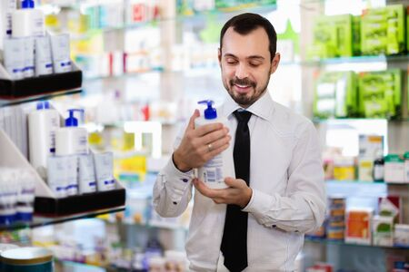 Smiling happy cheerful male customer looking for right medicine in pharmacy Stockfoto