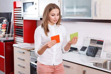 Positive woman looking for stylish materials for kitchen furnishing in store