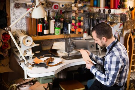 Professional man worker showing his workplace and tools in leather workshop