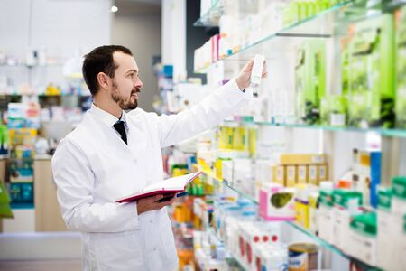 Happy young pharmacist writing down assortment of drugs in pharmacy