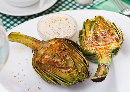 Concept of vegetarian food. Chopped fried artichokes sprinkled with koshering salt served with white sauce Stock fotó