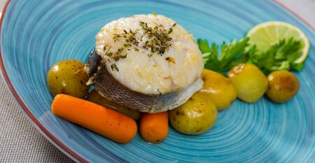 Steak of  codfish prepared and served with boiled potatoes, carrots and greens