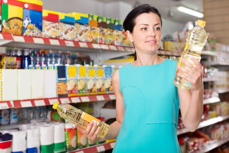 Smiling young woman choosing different oil in the modern supermarket