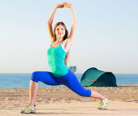 Happy woman in blue T-shirt is practicing stretching on the beach. Imagens
