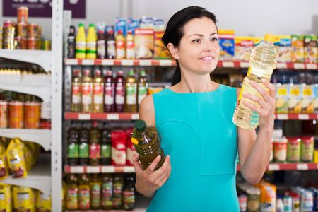 Smiling young woman choosing different oil in bottle at the supermarket Stock Photo