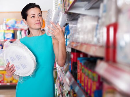 Woman choosing plastic plate and cup at the supermarket