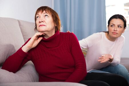 Portrait upset adult women looking away after conflict at home interior