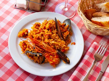 Appetizing racy seafood paella with mussels and prawns.Traditional Valencian cuisine Stock Photo