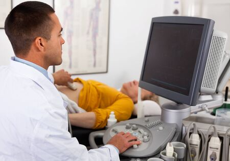 Young positive man sonographer using ultrasonography machine checking female patient in hospital diagnostic room