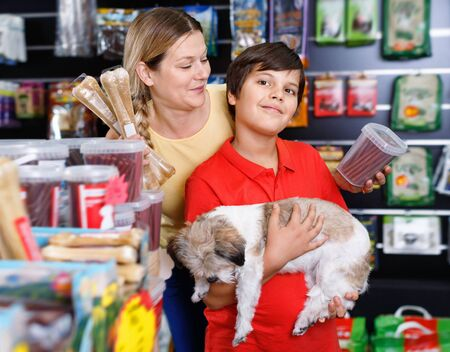 Careful preteen glad  positive  boy with mother visiting pet shop in search of treats for their dog Banco de Imagens