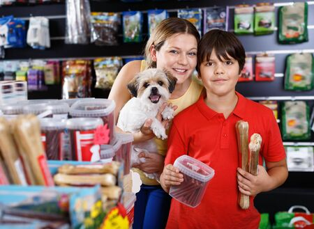 Careful preteen positive boy with mother visiting pet shop in search of treats for their dog
