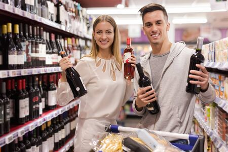 Young loving couple shopping wine for date in supermarket Standard-Bild