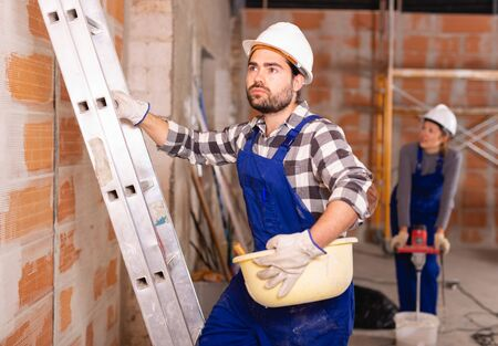 Portrait of builder in process of finishing work in cottage Reklamní fotografie