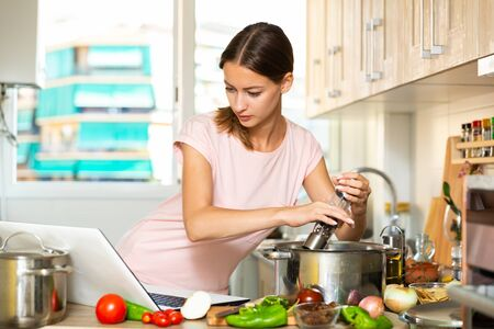 Portrait of positive girl cooking vegetable soup with help of laptop