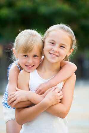 Portrait of two girls playmates outdoors in summer day