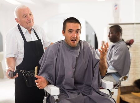 Young man unpleasantly surprised by haircut performed by elderly hairdresser at barber shop