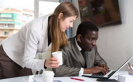Smiling female boss flirting with employee at workplace, harassment in office