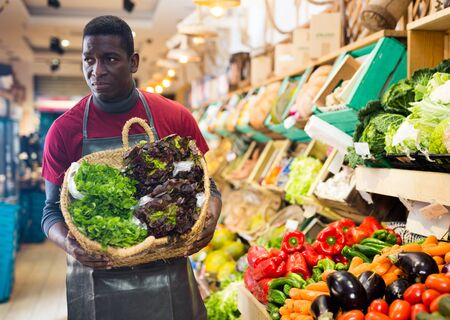 Confident African American seller in black apron arranging fresh leafy vegetables on greengrocery counter